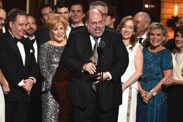 Scott Rudin, in a tuxedo, stands on stage holding a Tony, surrounded by the cast of Hello Dolly!
