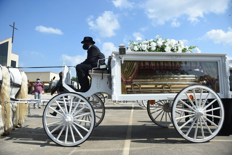A horse and buggy carry a glass box holding the casket of George Floyd.