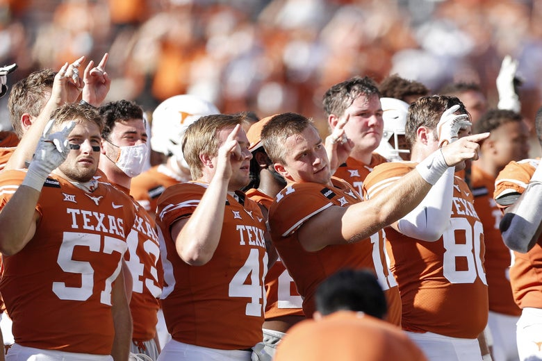 """The Texas Longhorns stand for The Eyes of Texas, making the """"Hook 'em Horns"""" gesture with their hands after the game"""