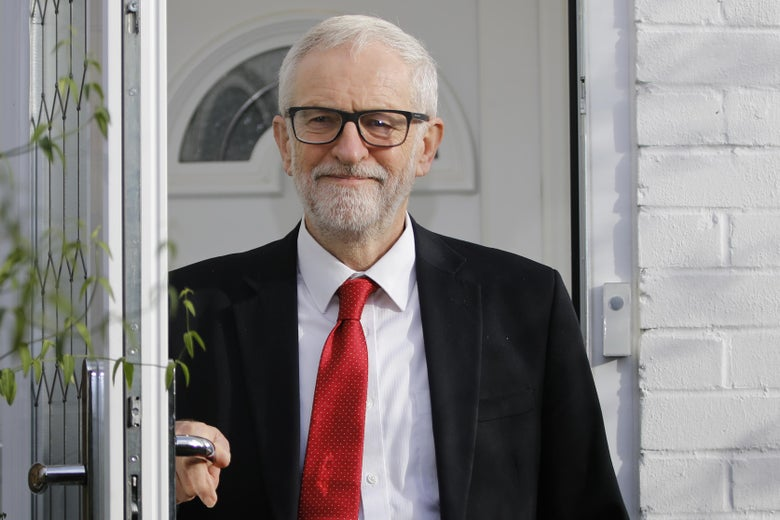 Jeremy Corbyn, wearing a suit, smiles while standing in his doorway.