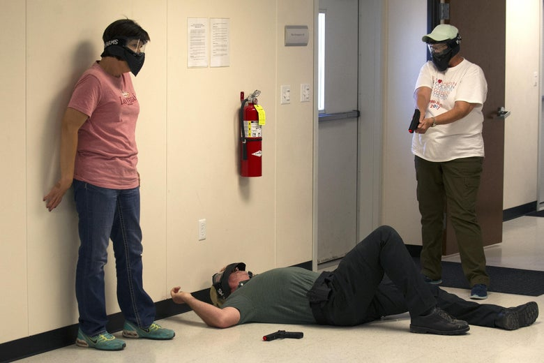 A person wearing a paintball mask points a pellet gun at a man lying on the ground in a hallway. Another person stands next to that man.
