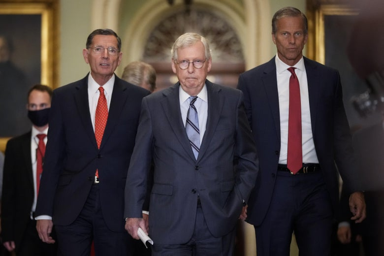 three old white men in suits walking