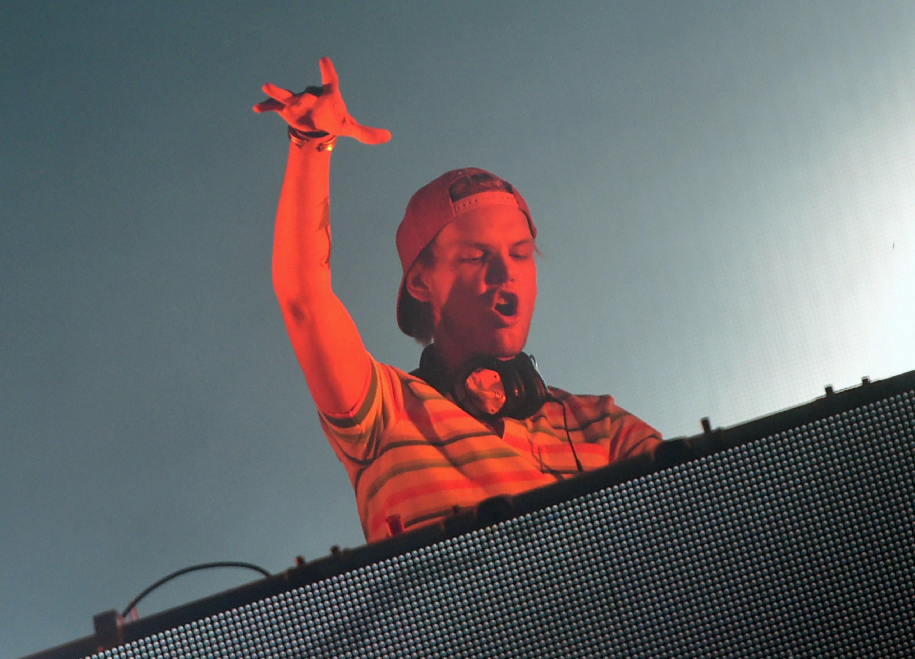 Avicii, wearing headphones around his neck, raises his hand from behind a turntable while onstage.