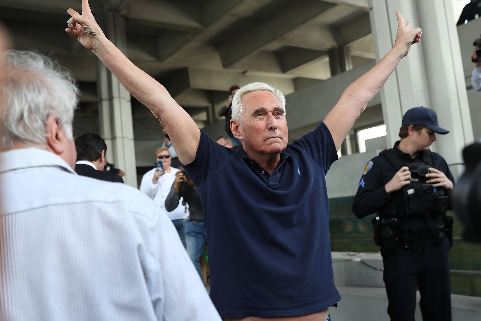 Roger Stone leaves the courthouse with both arms raised in a Nixon salute.