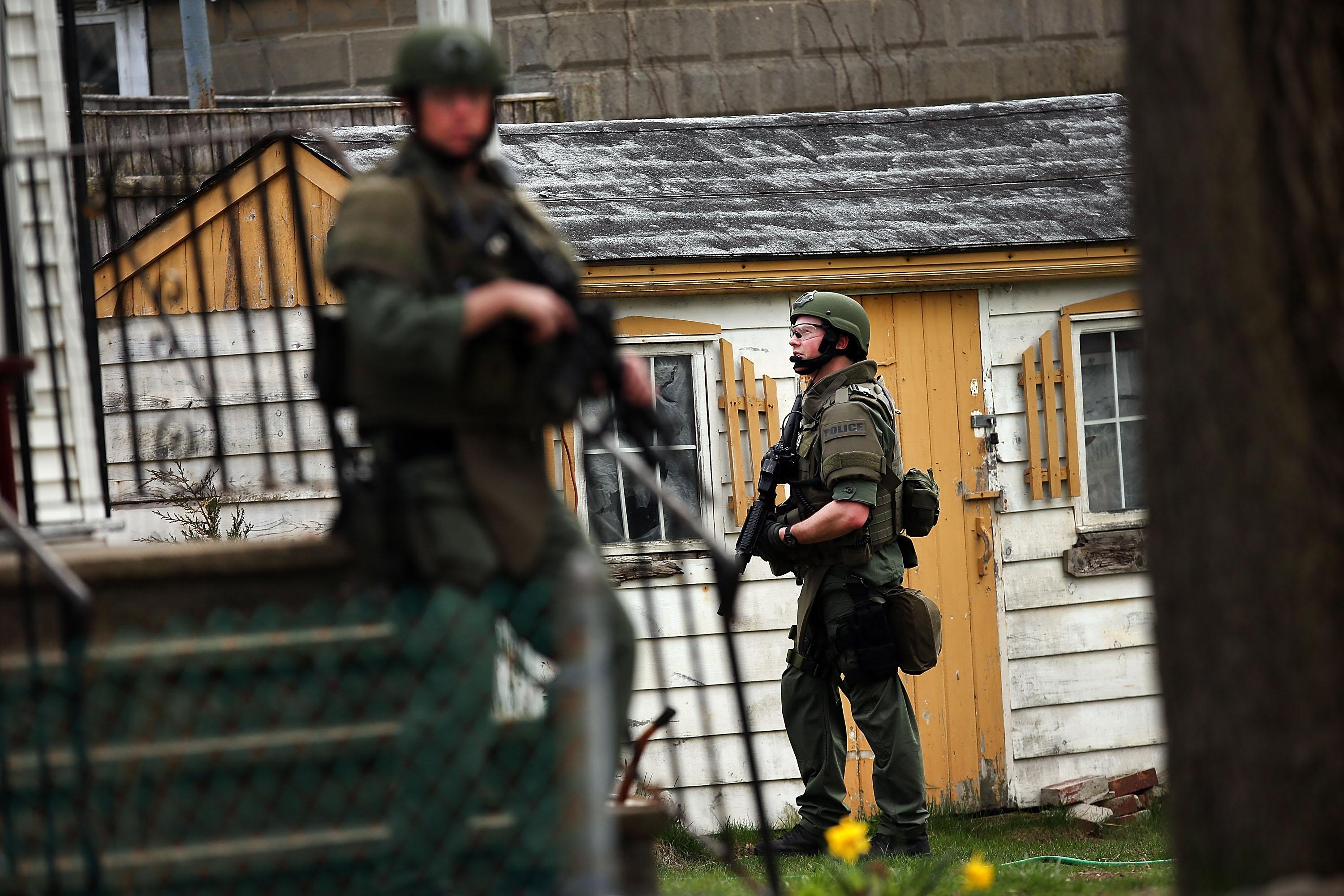 Members of a police S.W.A.T. team search through a neighborhood in Watertown