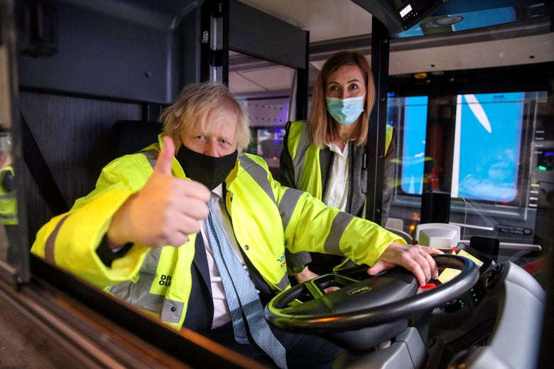 Boris Johnson wears a yellow high-visibility jacket and gives a thumbs-up as he sits behind the wheel of a bus.