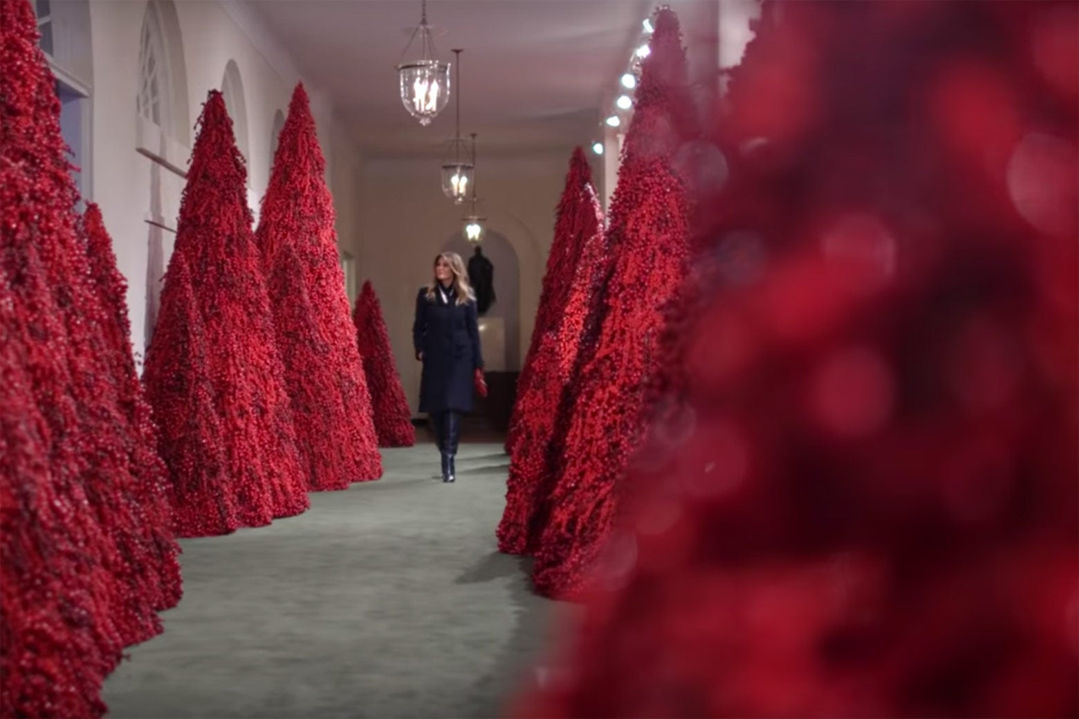 Melania Trump walks down a hallway lined with giant red textured cones.