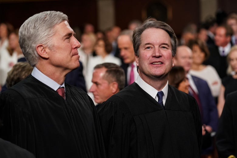 Neil Gorsuch and Brett Kavanaugh smile and stand in judicial robes.