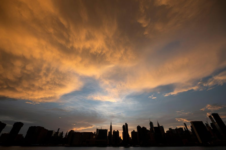 The sun sets behind the skyline of midtown Manhattan following a heat wave.