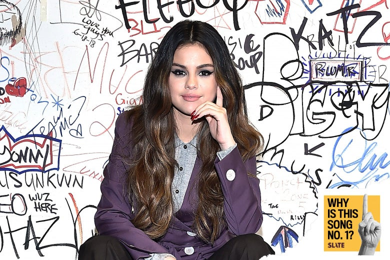 Selena Gomez in front of a wall with handwritten graffiti on it.