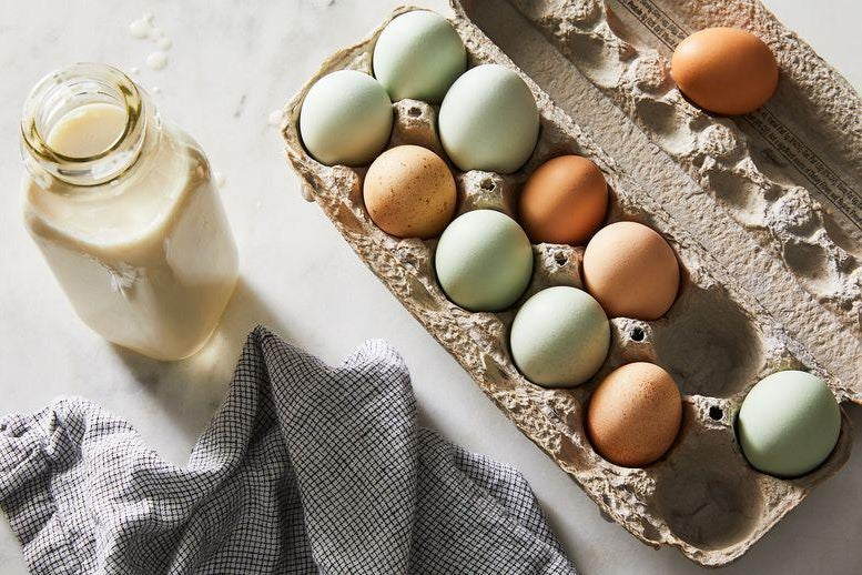 Eggs with brown and baby blue shells in a carton next to a glass bottle of cream.
