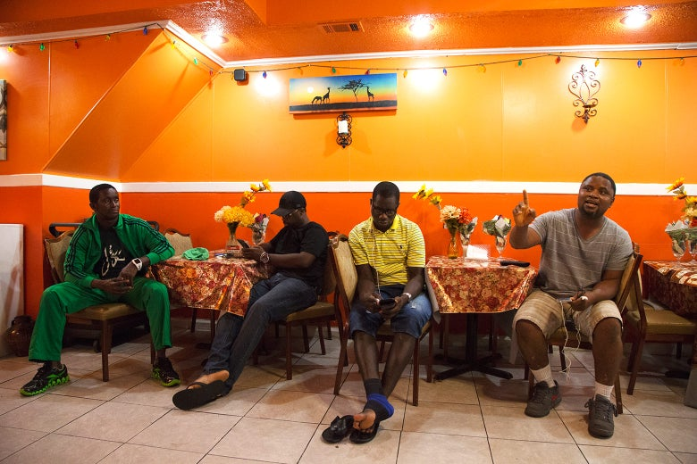 Men discuss the upcoming Sierra Leonean presidential election inside Tasty African restaurant on Woodland Avenue.