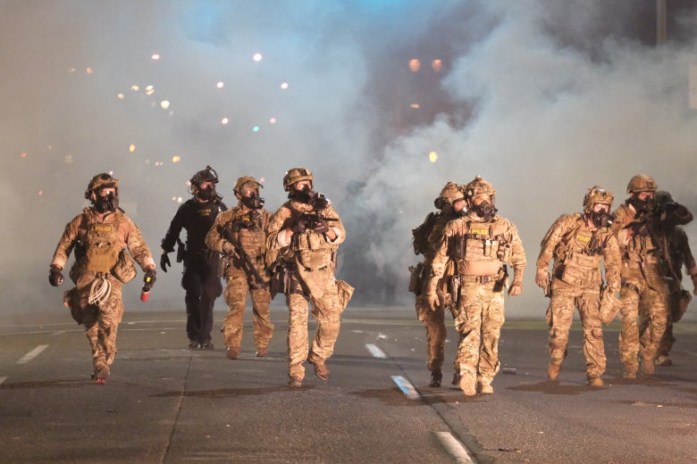 Officers in camo walk down a street at night amid smoke.
