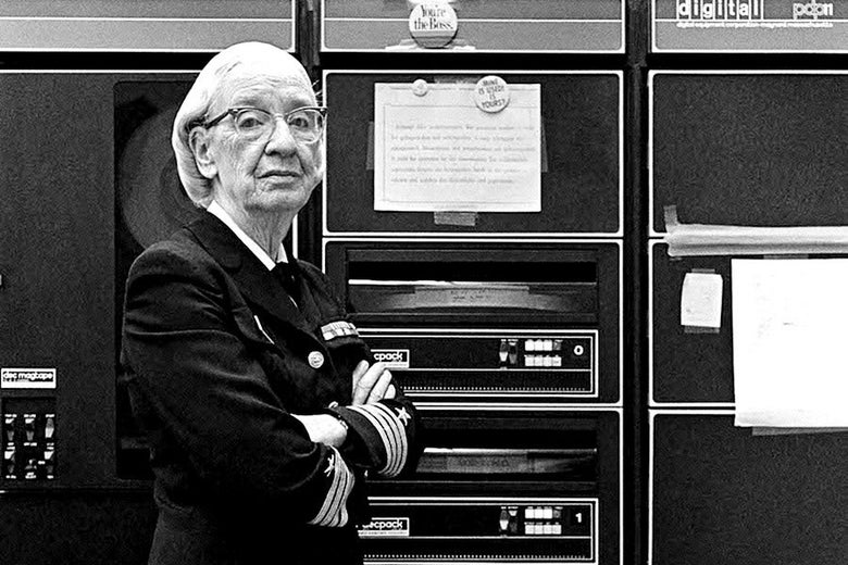 Grace Hopper stands in her Navy uniform, arms crossed, in front of a massive computer.