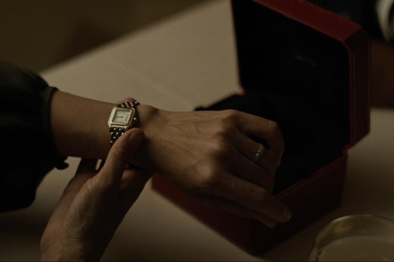 Wrist showing off a fancy gold watch in front of its case