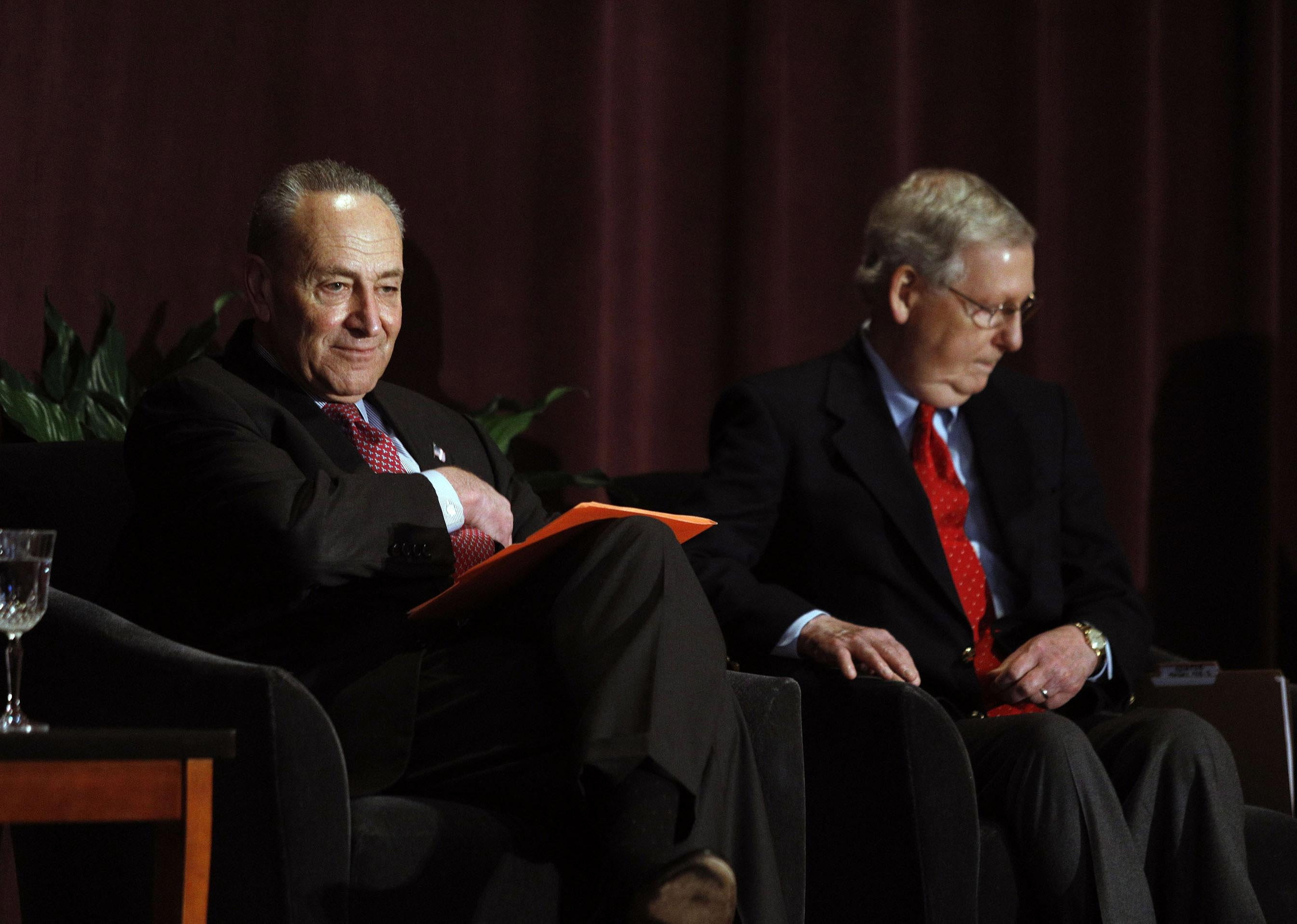 Mitch McConnell and Chuck Schumer sit on a stage in front of plants and a curtain.