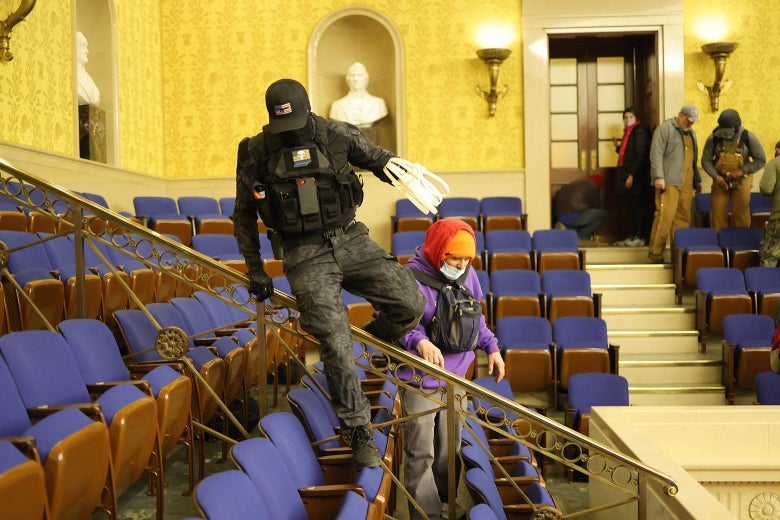 A man wearing black tactical gear and holding zip ties climbs over gallery seats in the Senate chamber.