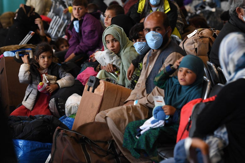 A family of Afghans crowded among others sitting and waiting