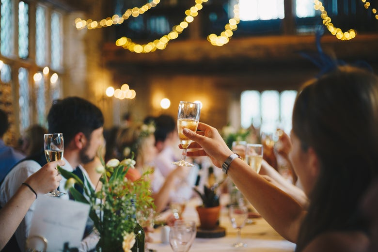 Wedding guests seated in a banquet hall toast the couple