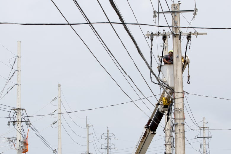 An employee of the Puerto Rico Electric Power Authority repairs a power line damaged by Hurricane Maria.
