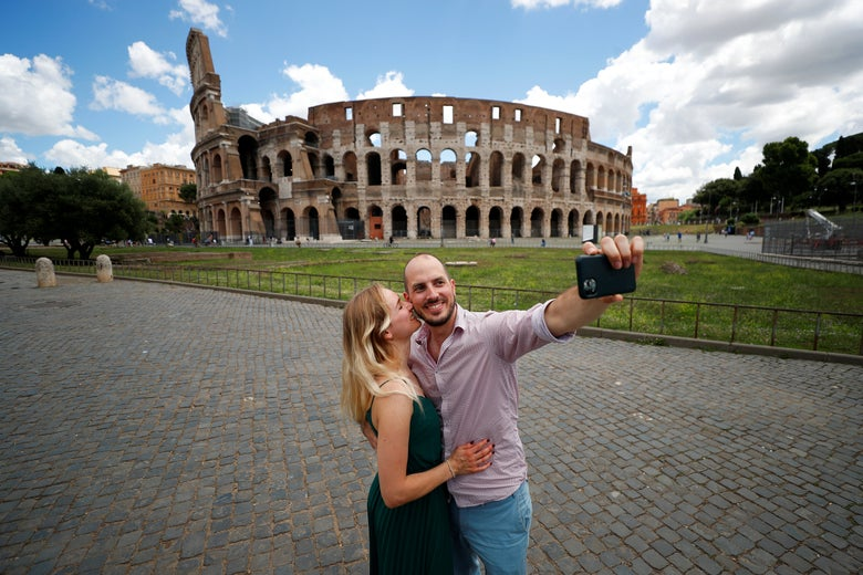 A couple taking a selfie in front of the Colosseum