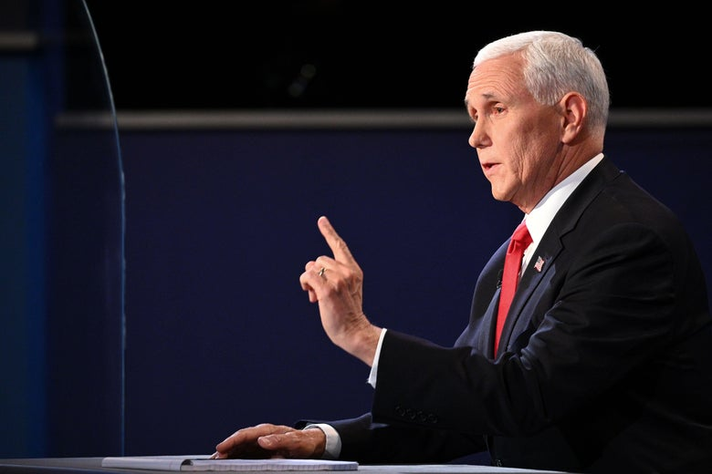 Mike Pence, in profile at the right side of the picture, speaks while sitting with his right hand flat on a desk and his left index finger wagging.