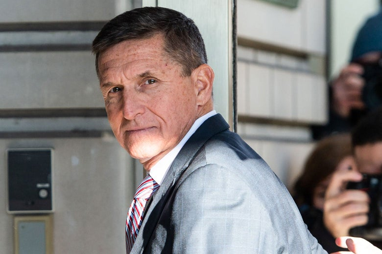 Outside the court building, Flynn turns to the camera, with more photographers in the background