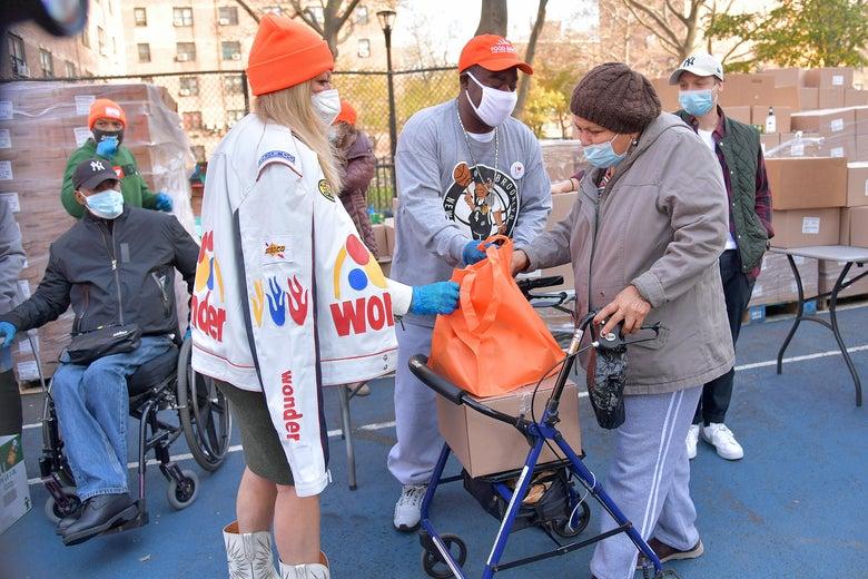 three people standing around an orange bag containing a turkey