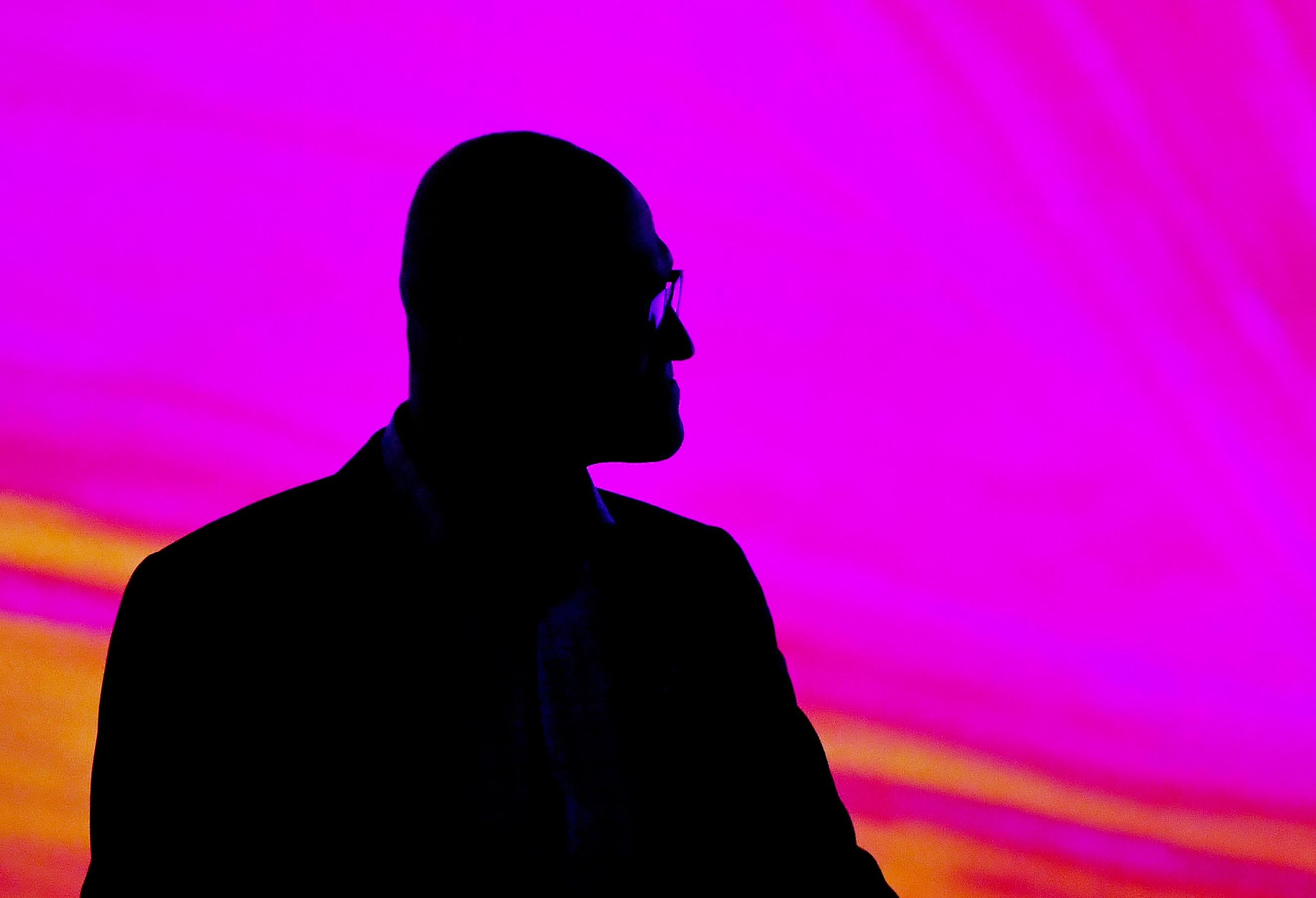 Satya Nadella seen in silhouette against a purple-red backdrop.