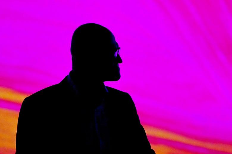 Satya Nadella seen in silhouette against a purple-red backdrop.