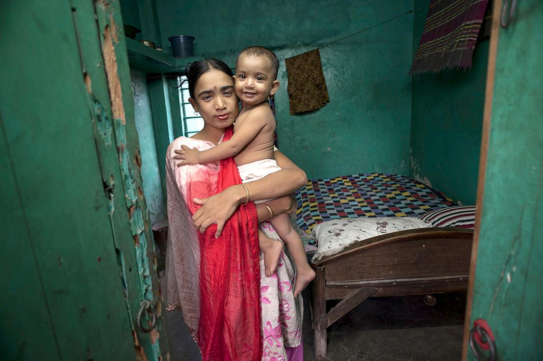 Labone, 27, takes a moment to hold her young daughter Nupur, 1, who was fathered by a client, before she has to return to her evening's work in a brothel in Jessore, Bangladesh.