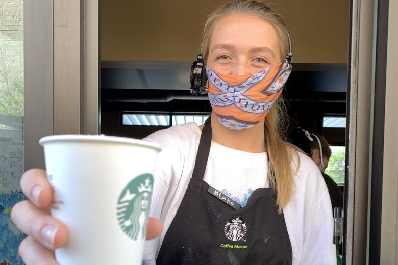 A Starbucks employee wears a facial covering while working the drive-thru during the coronavirus (COVID-19) pandemic on April 07, 2020 in Dallas, Texas.  Starbucks is requiring employees to wear a facial covering and is making thermometers available to employees who would like to take their temperature before starting a shift.