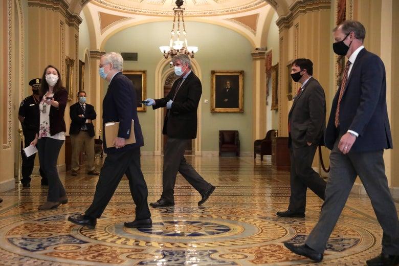 Men with face masks on walk through a hallway.