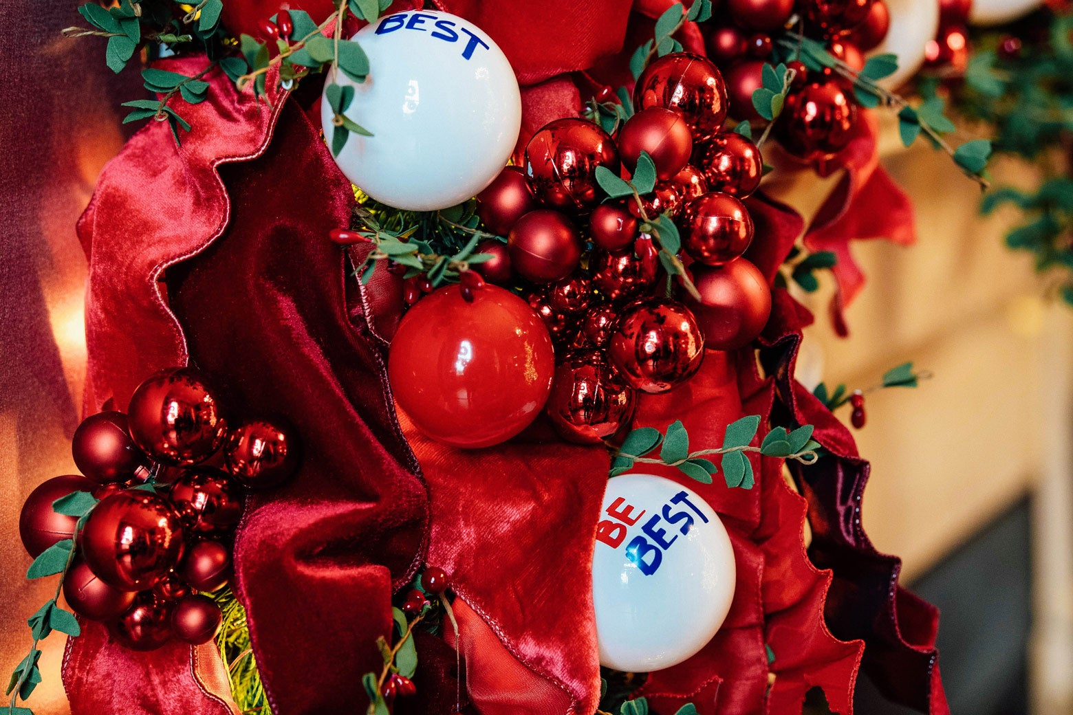 """White ornaments that say """"Be Best"""" are surrounded by red ribbons, fake holly berries, and red Christmas balls."""