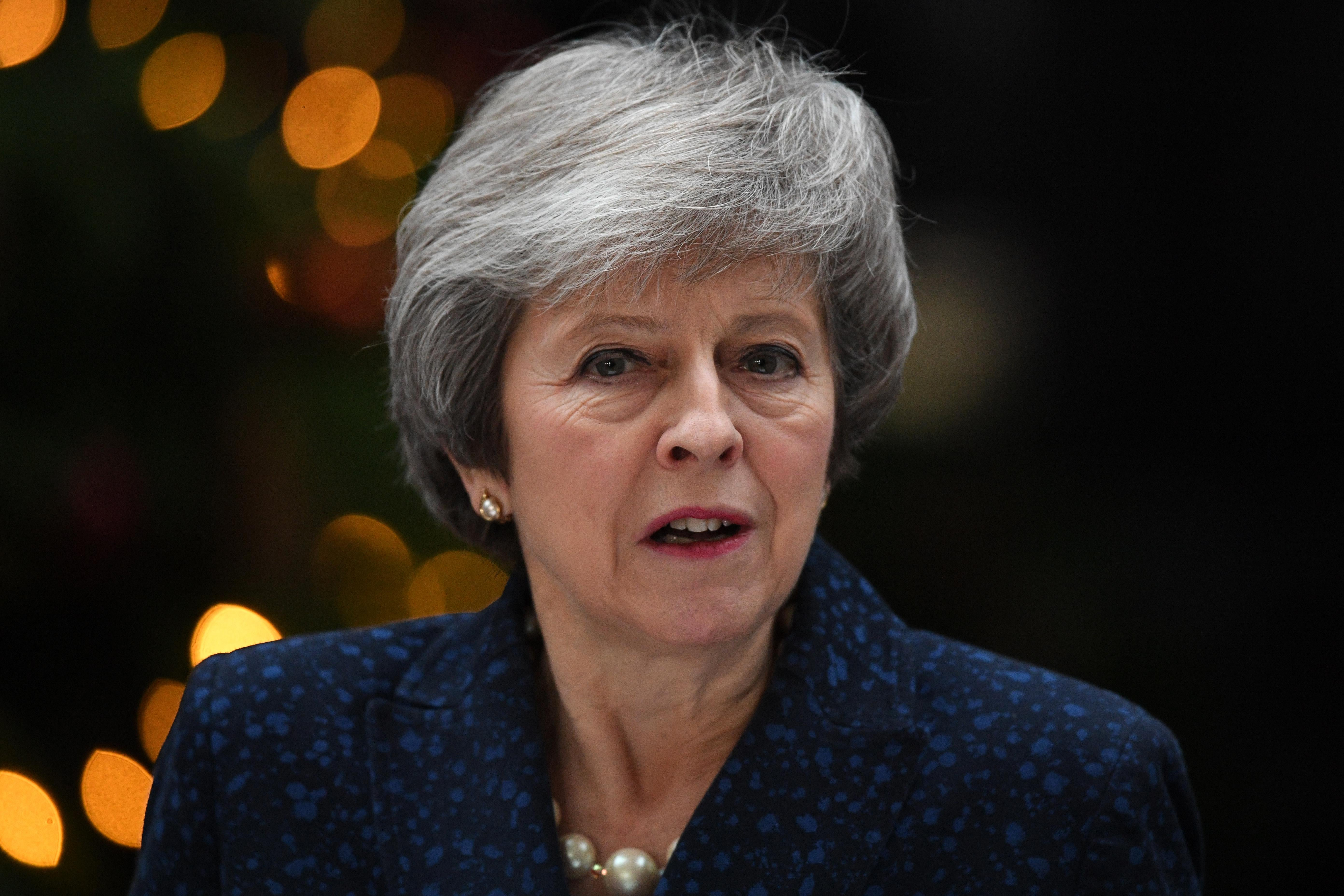 Theresa May speaks and looks toward the camera. Behind her, there appear to be Christmas lights.