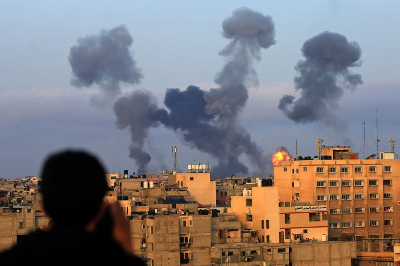 A Palestinian boy watches from a distance as smoke billows from the skyline during Israeli airstrikes on the southern Gaza region of Khan Yunis.