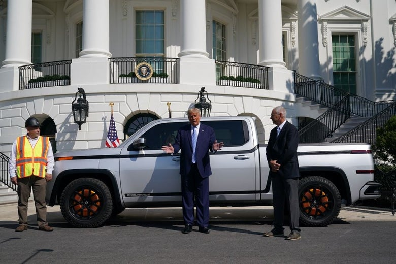 Trump, standing in front of a pickup truck outside the White House, gestures while speaking.
