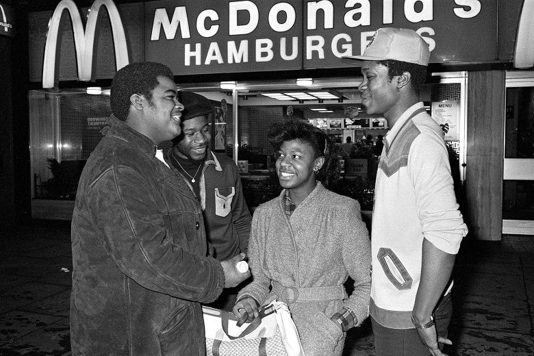 Black-and-white photo of four black teens smiling and standing outside a McDonald's.