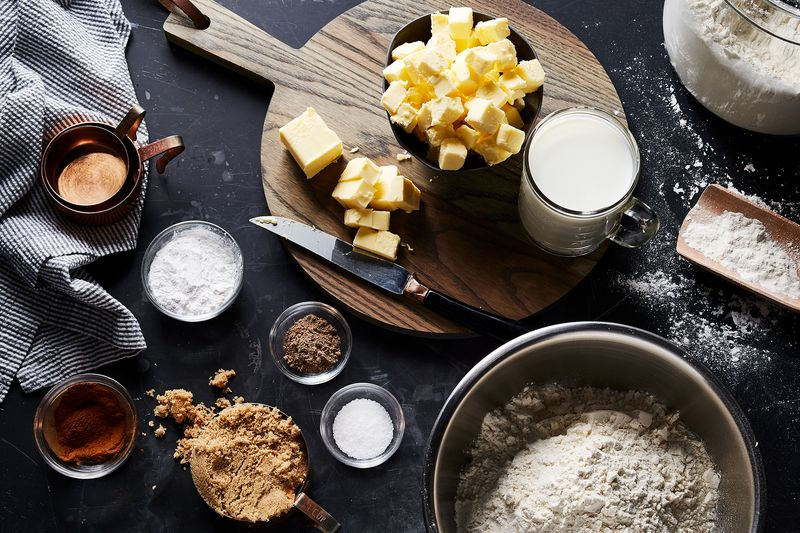 An array of various ingredients: chunks of butter, salt, brown sugar, flour, milk, cardamom, salt, and baking powder.