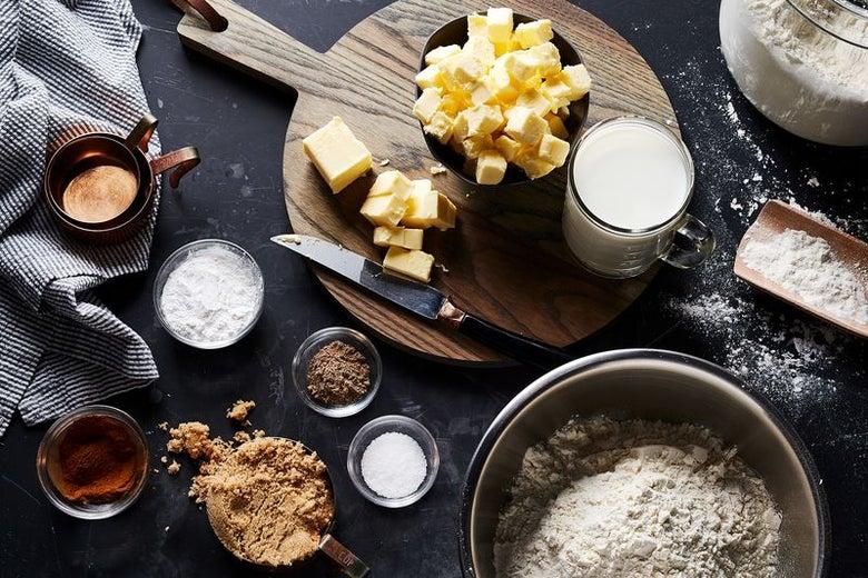 An array of various ingredients: chunks of butter, salt, brown sugar, flour, milk, cardamom, salt, and baking powder.