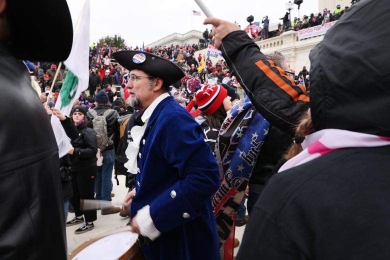 A man dressed in colonial garb stands among a mob of people outside the Capitol.