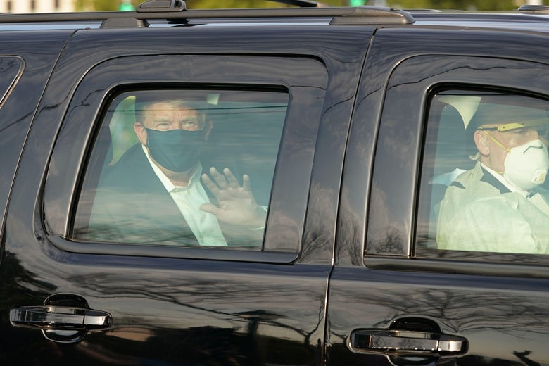 Trump, wearing a mask, waves from the back of a car. His driver is also wearing a mask.