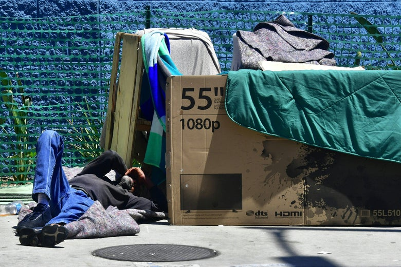 A homeless man sleeps beside his makeshift temporary shelter on a street in downtown Los Angeles, California on June 25, 2018.