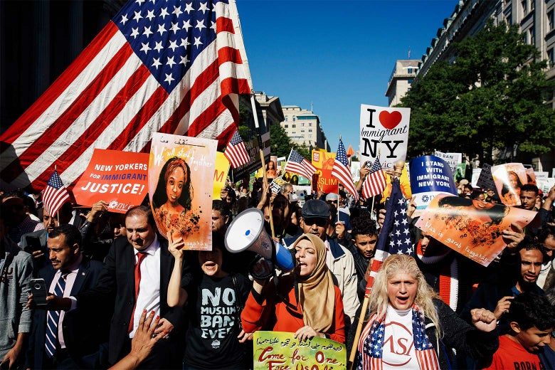 Activists march toward Trump International Hotel during a protest against the Trump administration's proposed travel ban on Oct. 18 in Washington.