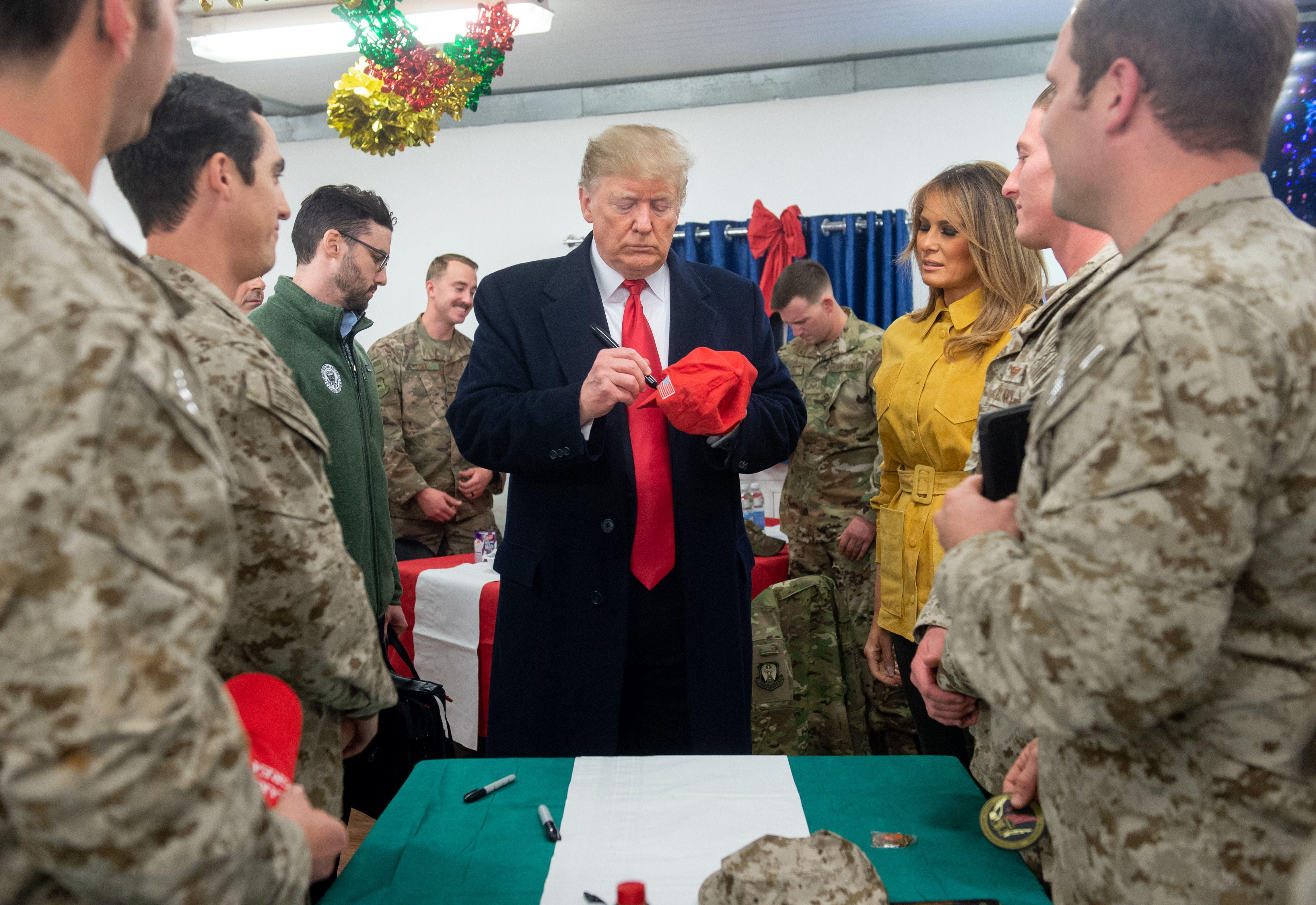 President Donald Trump signs a hat as First Lady Melania Trump looks on as they greet members of the U.S. military during an unannounced trip to Al Asad Air Base in Iraq on December 26, 2018.