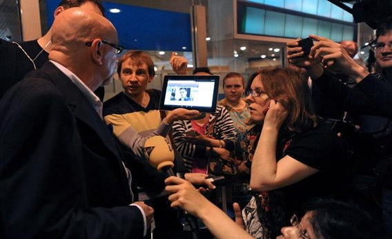 A journalist shows to a passenger a picture of former US spy Edward Snowden on a tablet, at the arrival gate of the Moscow Sheremetevo airport on June 23, 2013.
