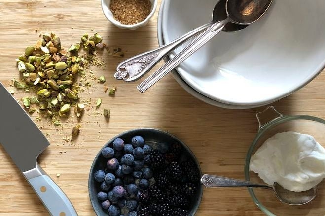 Berries, chopped nuts, and cream on a countertop.