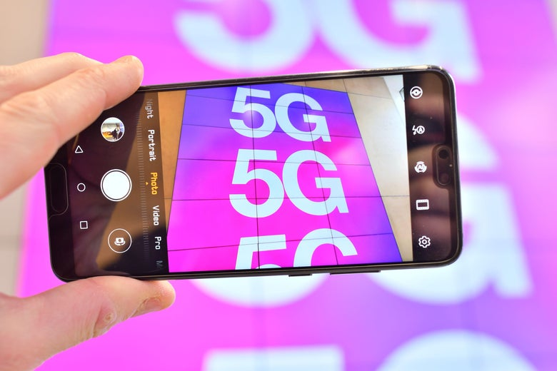 A phone being held up to photograph 5G signage.