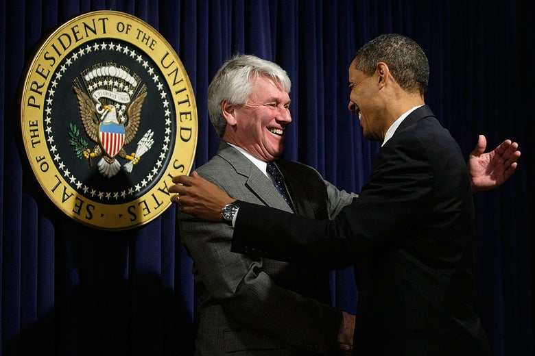Craig and Obama shake hands in front of a presidential seal.