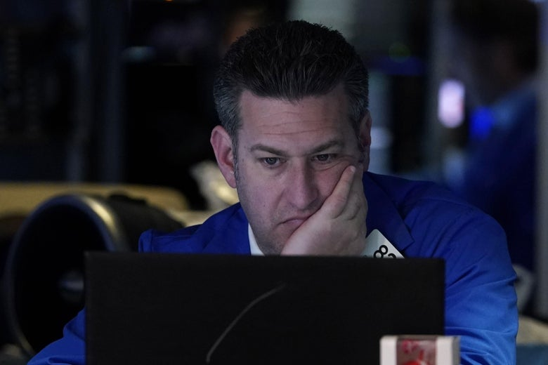 A man in a blue coat sits at a computer with his head in his hand.